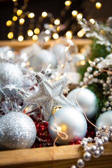 Bellissimo bokeh sfondo di natale. rami di abete, decorazioni natalizie, coni, palline rosse e d'argento, perline rosse