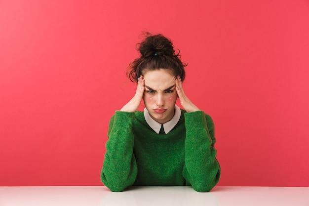 Bella ragazza annoiata giovane studente seduto al tavolo isolato