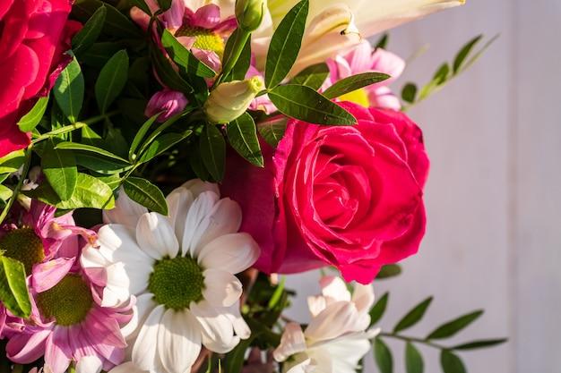 Bellissimo bouquet di fiori diversi in una scatola su fondo di legno bianco.