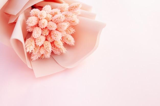 Bello mazzo dei fiori rosa asciutti su un fondo bianco di legno