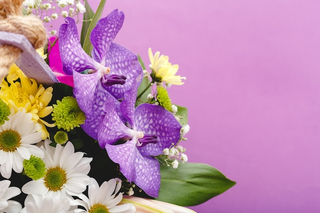 Bellissimo mazzo di fiori in cesto di legno lilla su sfondo viola. orchidee, crisantemi, gigli, composizione floristica floreale di camomille.