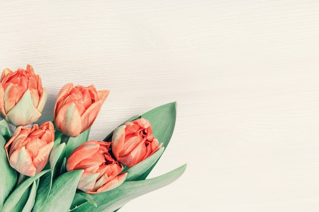 Bellissimo bouquet di tulipani arancioni su un tavolo di legno bianco