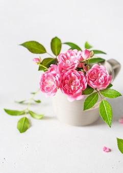 Bellissimo bouquet di mini rose rosa in una tazzina da caffè espresso