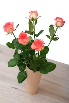 Bellissimo bouquet di rose rosa in vaso di ceramica sul tavolo in uno sfondo bianco. concetto di celebrazione.
