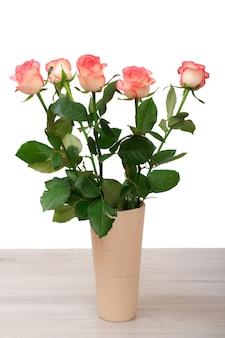 Bellissimo bouquet di rose rosa in vaso di ceramica sul tavolo in sfondo bianco isolato. concetto di celebrazione.