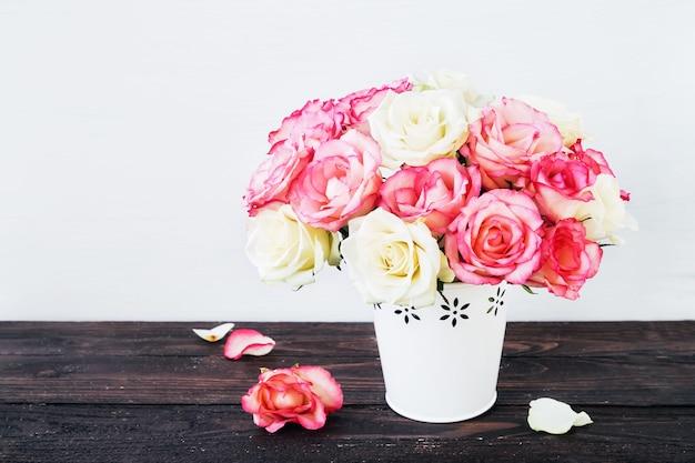 Bellissimo bouquet di rose rosa e bianche in vaso bianco sulla tavola di legno