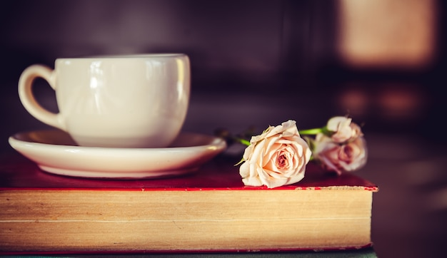 Bellissimo mazzo di rose al sole sui libri con una tazza