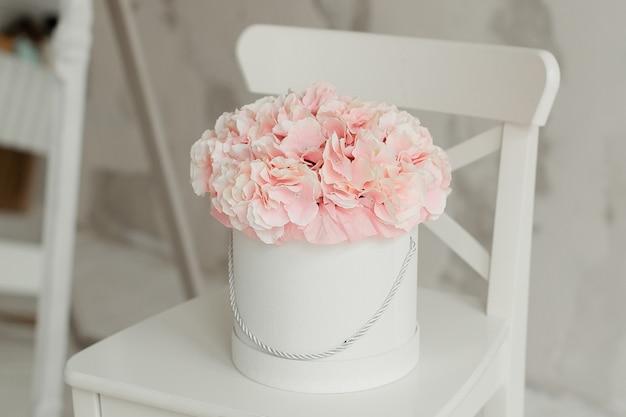 Un bel mazzo di fiori estivi in una scatola rotonda su uno sfondo di muro bianco. fiori decorativi all'interno.