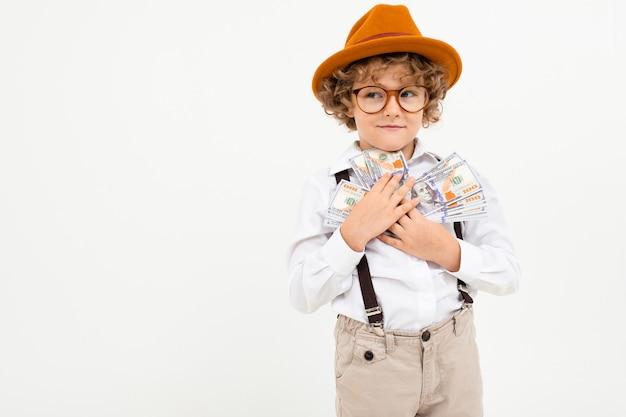 Il bello ragazzo con capelli ricci in camicia bianca, il cappello marrone, vetri con le bretelle nere giudica i soldi isolati su bianco