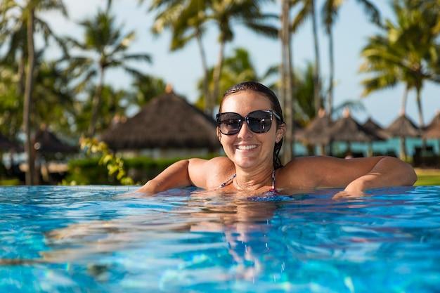 Bella donna brasiliana che gode delle vacanze di vacanza al lussuoso resort hotel fronte mare con piscina e paesaggio tropicale vicino alla spiaggia