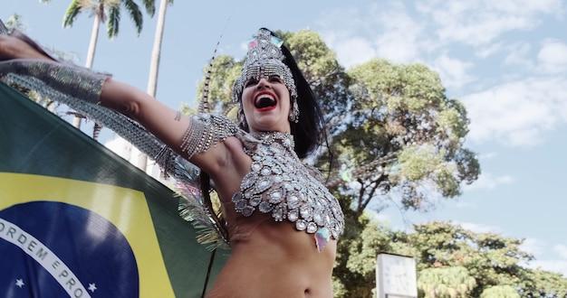 Bella donna brasiliana che indossa costumi di carnevale colorati e bandiera del brasile durante la sfilata di carnevale in città.