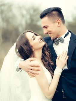 Bella coppia di sposi di giovane uomo che abbraccia felice bella donna all'aperto