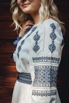 Bella sposa in una camicia ricamata sullo sfondo di una casa in legno. dettagli del modello.