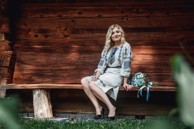 Bella sposa in una camicia ricamata con un mazzo di fiori sullo sfondo di una casa in legno.