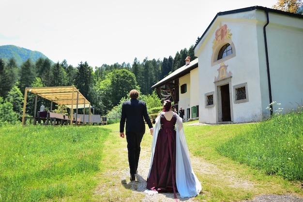 Bella sposa in un vestito costoso che cammina nei boschi in natura tenendosi per mano