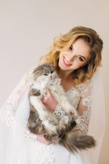 La bella sposa tiene il gatto lanuginoso con il farfallino sullo sfondo del muro guarda la telecamera