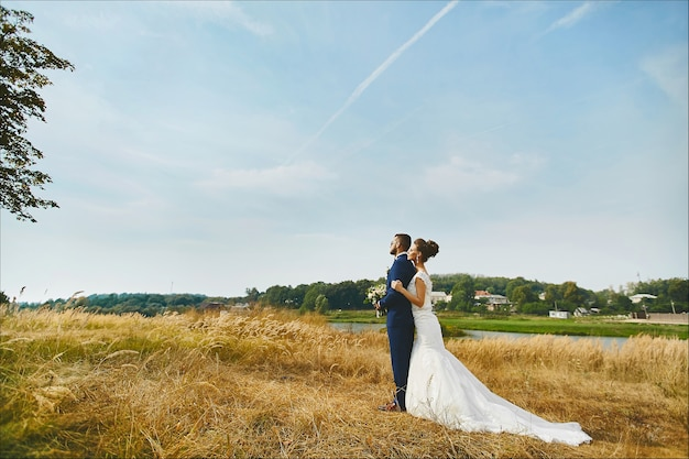 Bella sposa che abbraccia teneramente lo sposo in un campo di grano da qualche parte nella coppia di innamorati della campagna