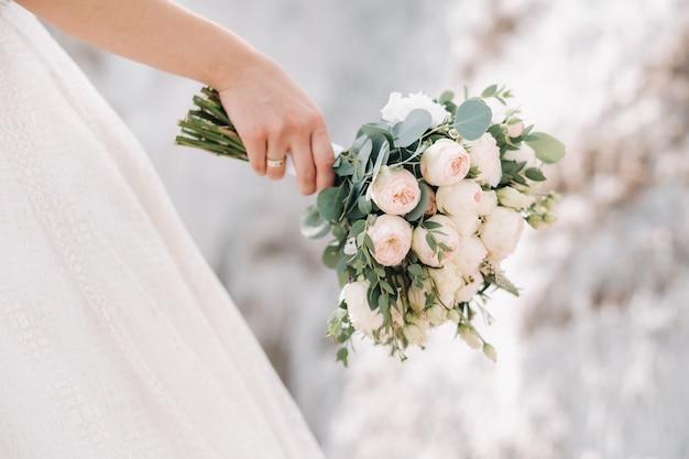 La bella sposa sta tenendo un mazzo variopinto di nozze. la bellezza dei fiori colorati. mazzo di fiori del primo piano. accessori da sposa. decorazione femminile per ragazza. dettagli per matrimonio e per sposi