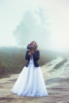 Bella sposa e una giacca di pelle con un bouquet sullo sfondo di un campo nebbioso