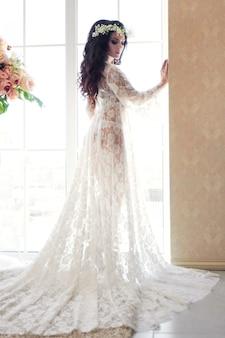 Bella sposa in lingerie e con una corona di fiori in testa, la mattina prima del matrimonio. vestaglia bianca della sposa, preparando per la cerimonia nuziale. ragazza sexy sul letto