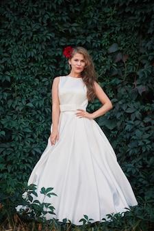 Bella sposa in un lussuoso abito da sposa con un fiore tra i capelli su uno sfondo naturale verde
