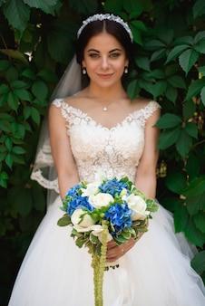 Bella sposa all'aperto in una foresta, giorno delle nozze.