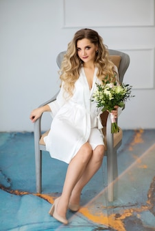 Bella sposa in vestaglia su una sedia