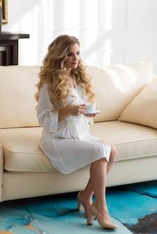 Bella sposa in vestaglia sul divano con una tazza di caffè