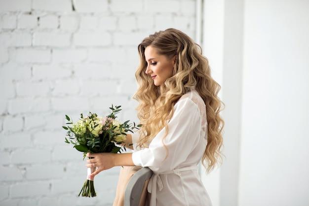 Bella sposa in vestaglia con un bouquet da sposa di profilo