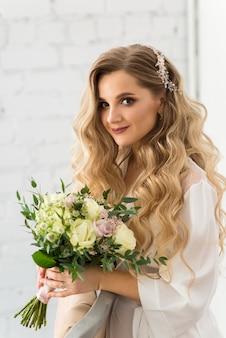 Bella sposa in vestaglia con bouquet da sposa
