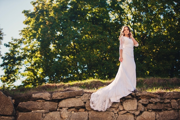 Bella sposa in posa vicino alle rocce su uno sfondo di natura