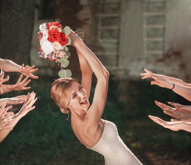La bella sposa getta il bouquet da sposa ai suoi amici