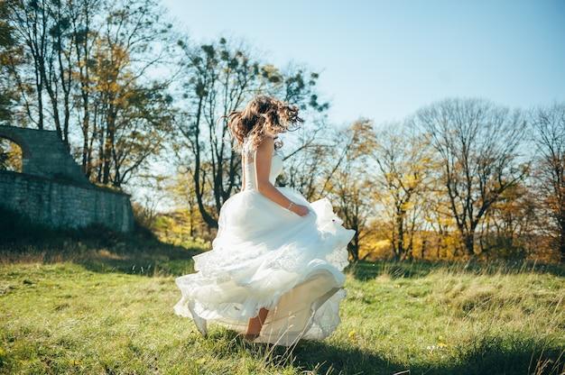 Bella sposa in un abito da sposa nel parco in autunno