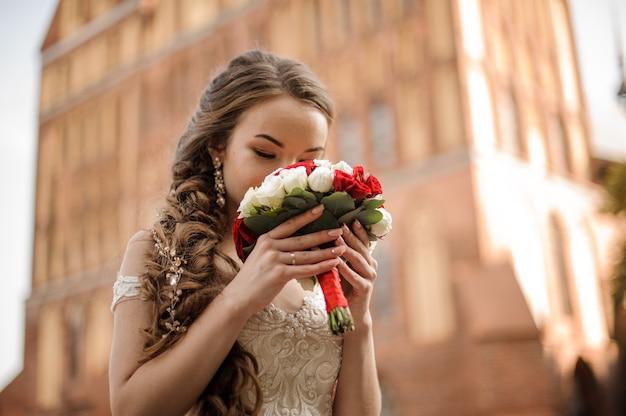Bella sposa in un abito da sposa con un'acconciatura a treccia annusando un bouquet di rose rosse e bianche sullo sfondo dell'edificio