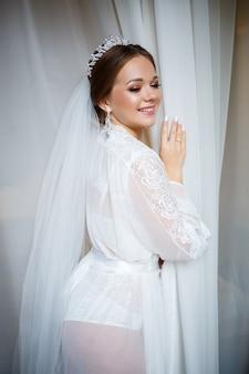 Bella sposa in una mattina di nozze in accappatoio e velo