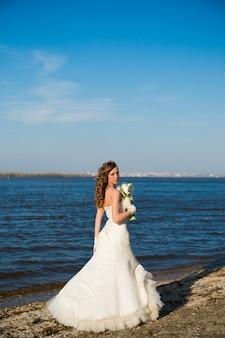 Bella sposa in abito bianco sulla costa del fiume in estate