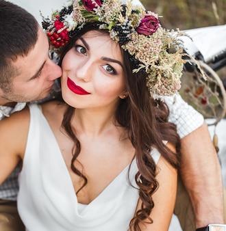 Bella sposa in un abito bianco e una corona di fiori sulla natura. mazzo. nozze. fiori