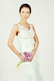 Bella sposa in abito bianco con bouquet