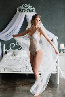 Bella sposa in lingerie bianca sdraiata sul letto nella sua camera da letto