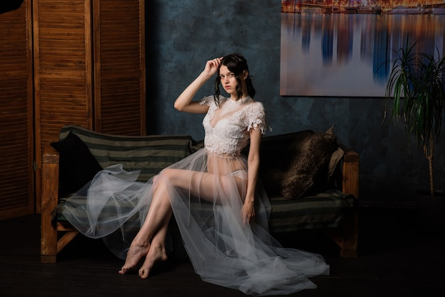 Bella sposa in biancheria bianca che si siede nella sua camera da letto e studio. mattina del concetto di matrimonio