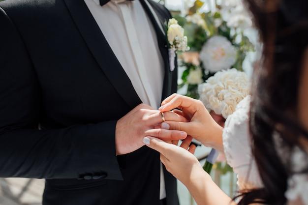 La bella sposa in vestito da sposa bianco mette sul dito dello sposo l'anello nuziale