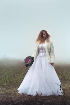 Bella sposa con un bouquet su uno sfondo di un campo nebbioso