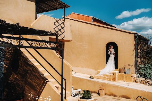 Una bella sposa dai lineamenti piacevoli in abito da sposa viene fotografata in provenza.