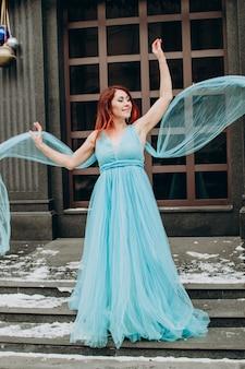 Bella sposa con i capelli rossi in un abito lungo blu sullo sfondo della città