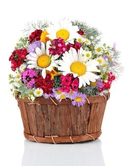 Bellissimi fiori luminosi nel cestino di legno su bianco