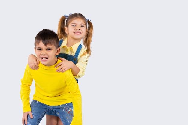 Bellissimi bambini luminosi fanno facce sorridenti e in posa su uno sfondo bianco con spazio laterale vuoto.