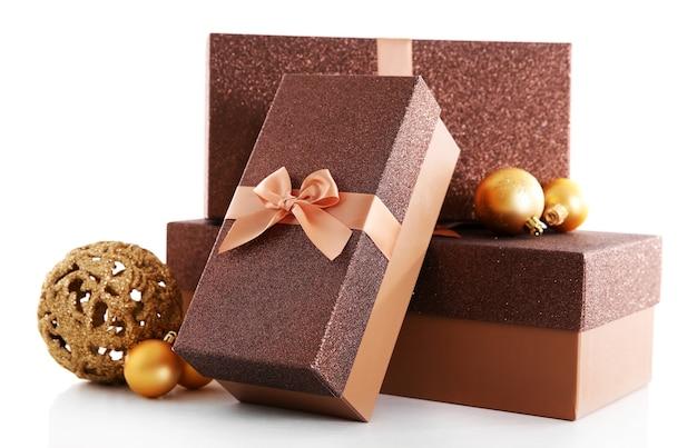 Bellissimi regali di natale marroni con giocattoli isolati su superficie bianca