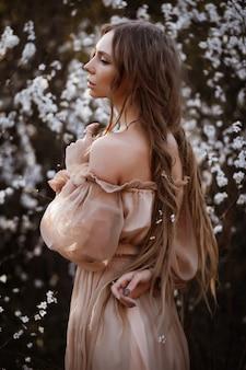 Bellissimo vestito marrone con spalle scoperte. ritratto di una bellissima modella in primavera. capelli lunghi