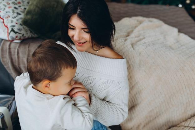 Bella mamma dai capelli castani e figlio adorabile del ragazzo che si siedono sul pavimento che abbracciano e che giocano