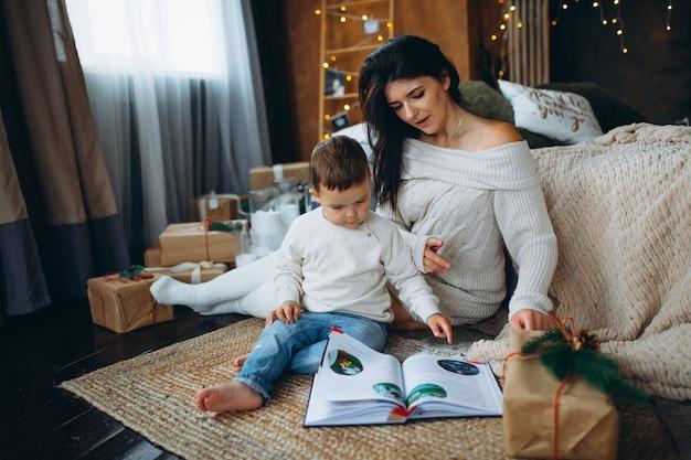 Bella mamma dai capelli castani e figlio adorabile ragazzo seduto sul pavimento e leggendo un libro di fiabe